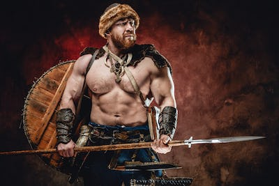 Nordic warrior with spear and shield on his back in dark background