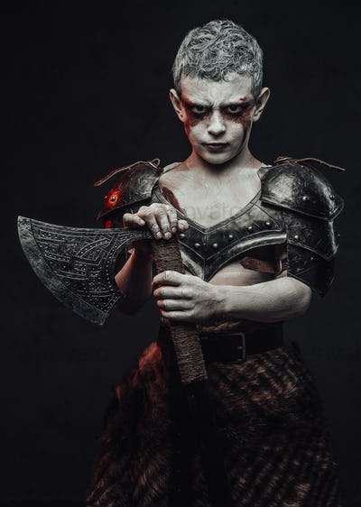 Holding an axe little barbarian with painted skin in dark background