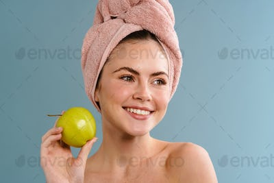 Half-naked happy girl in towel smiling and posing with apple