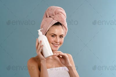 Nice happy girl wearing towels posing with body lotion