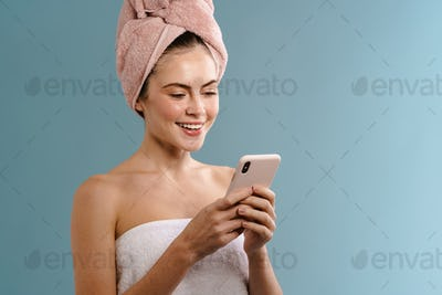 Nice happy girl wearing towels smiling and using mobile phone