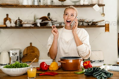 Beautiful surprised woman talking on cellphone while making lunch