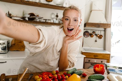 Astonished woman taking selfie and expressing surprise while making lunch