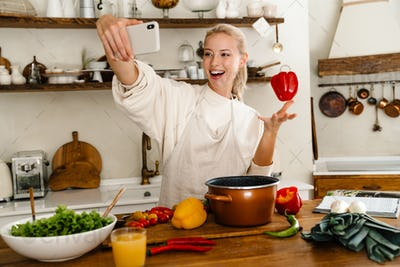 Woman excited selfie with bell pepper on cellphone while making lunch