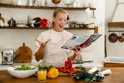 Beautiful excited woman reading cookbook and flipping bell pepper
