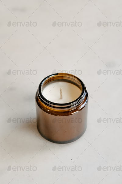 Candle in brown glass on white minimalist product photo