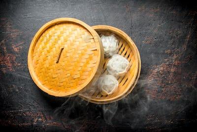 Hot dumplings manta in a bamboo steamer.