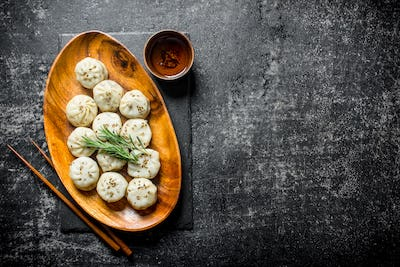 Freshly cooked dumplings manta on a plate with rosemary.