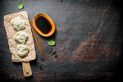 Dumplings manta on a cutting Board with soy sauce.