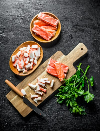 Chopped crab sticks with a knife and parsley.