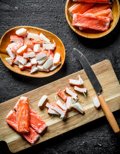 Sliced crab sticks on a cutting Board with a knife.