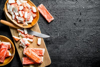 Pieces of crab sticks on a wooden cutting Board with a knife.