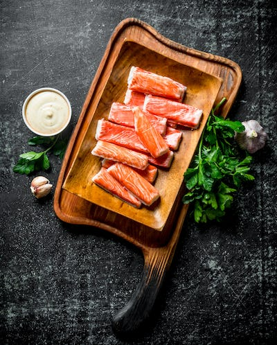 Crab sticks on a cutting Board with greens, sauce and garlic.