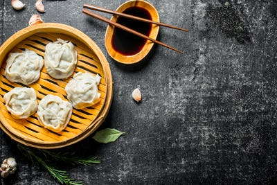 Traditional food. Manta dumplings in bamboo steamer with soy sauce.