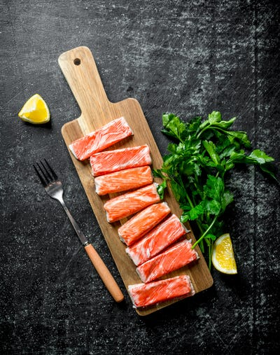 Crab sticks on a chopping Board with parsley and lemon.