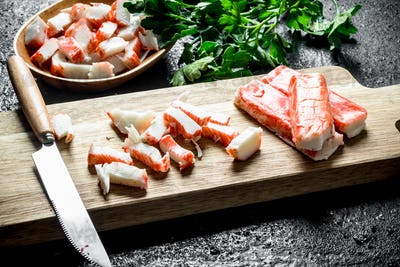 Pieces of crab sticks on a cutting Board and a plate of parsley.