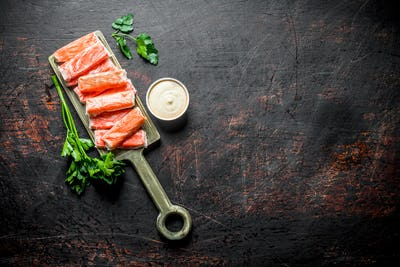 Crab sticks on a cutting Board with sauce and parsley.