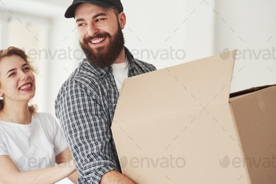 Sincere smiles. Happy couple together in their new house. Conception of moving
