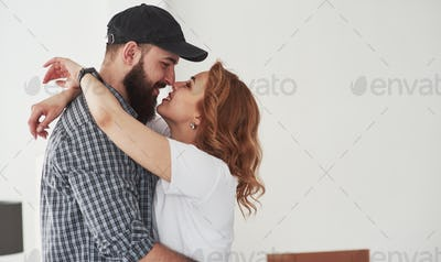 Kissing each other. Happy couple together in their new house. Conception of moving