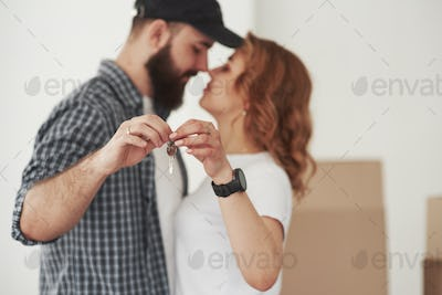 Holding keys. Happy couple together in their new house. Conception of moving