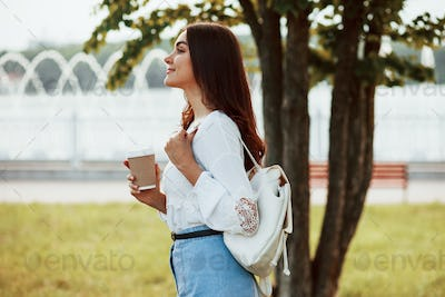In casual clothes. Young woman have good time in the park at her weekend