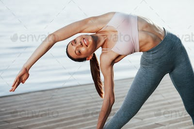 Feeling good. Young woman with slim type of body does exercises against lake
