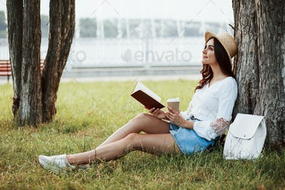 Attractive smiling girl. Young woman have weekend and sits in the park at daytime