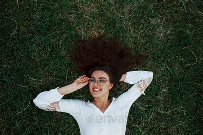 Wearing glasses. Girl lying down on the green grass and have a rest
