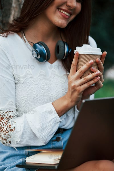 Headphones on the neck. Young woman have weekend and sits in the park at daytime