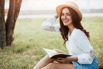 Notes in hands. Young woman have weekend and sits in the park at daytime
