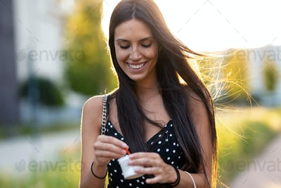 Beautiful young woman smiling while eating an ice cream standing in the street.