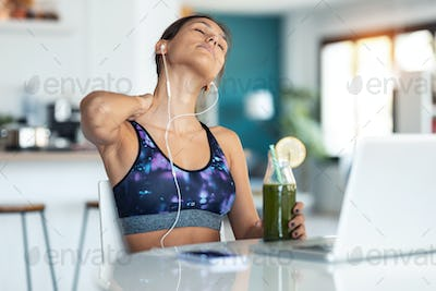 Tired young sporty woman suffering neck pain while drinking detox juice in the kitchen at home.