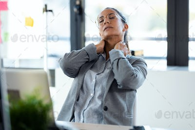 Tired young woman with neck pain working with her computer in the office