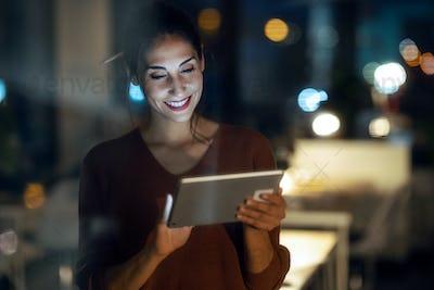 Smart pretty business woman taking a break cheaking her digital tablet in the office.