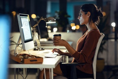 Beautiful young business woman working with computer while drinking coffee sitting in the office.