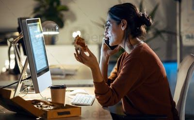 Beautiful young business woman working with computer while eating pizza sitting in the office.