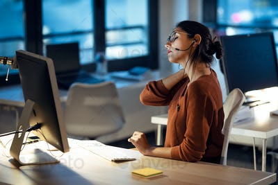 Tired business woman with back pain looking uncomfortable while working with computer in the office.