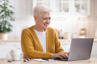Happy senior woman sitting in kitchen, using laptop computer