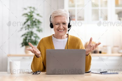 Happy old woman using laptop, having video call
