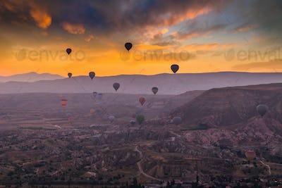 Hot air balloons flying over a volcanic landscape at Cappadocia, Turkey
