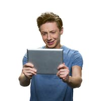 Teen skinny guy is holding tablet pc