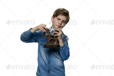 Teenage boy in denim clothes is making a shot with retro camera