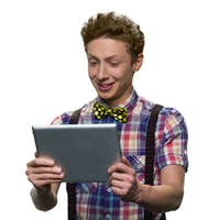 Teenage boy with facial expression of bewilderment or discontent is looking at tablet pc