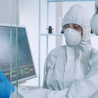 Biochemists in coverall typing on digital display vaccine composition