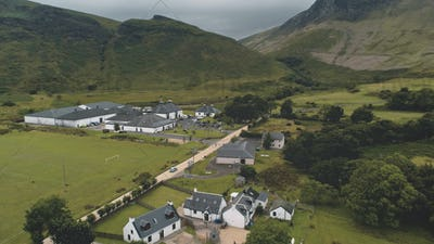 Arran whiskey distillery aerial. Road in green mountains valley. Scottish village with houses, camp