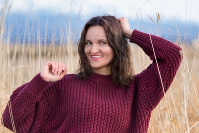 Portrait of Pretty Young Woman in Brown Sweater Stands in Dried Grass in Field