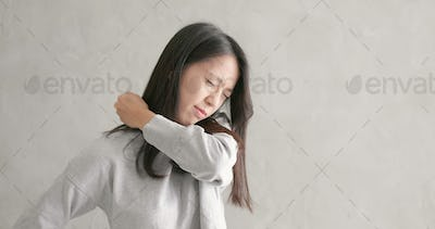 Woman feeling pain on shoulder over gray background