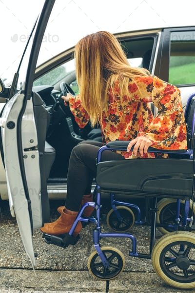 Woman in wheelchair getting on car