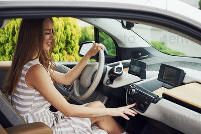 Turns the knob. Female driver inside of modern automobile. Testing brand new car