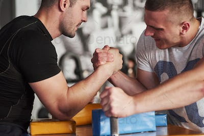 Beginning of the battle. Arm wrestling challenge between two men. Match on a special table